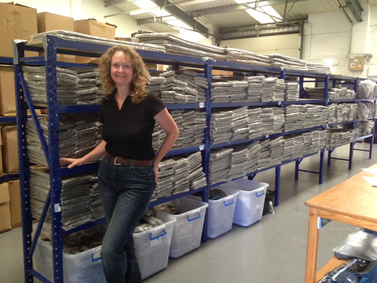 Sally owner of Chimney Sheep - standing by full shelves of Chimney Sheep