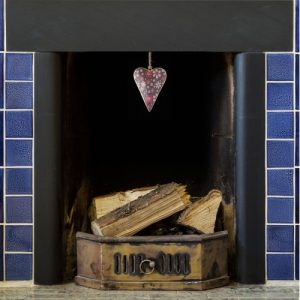 hand painted metal brown heart with red and pink flowers dangling from a blue tile fireplace