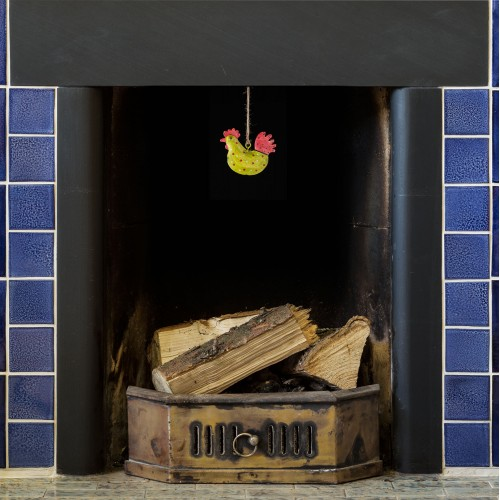 hand painted green and red spotted rooster dangling from a blue tiled fireplace