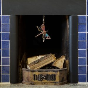 iridescent tin and copp[er dragonfly dangling from a blue tiled fireplace featuring vivid blues and golds.