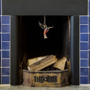 Iridescent tin and copper humming bird dangling froma blue tile fireplace featuring brigh colours of blue purple gold and red.