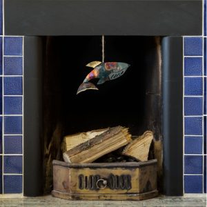 iridescent tin and copper whale dangling from a blue tiled fireplace featuring pretty vivid colours