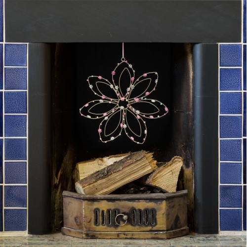 white wire flower with pink beads dangling from a blue tile fireplace