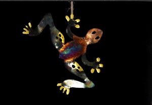 Dangling copper iridescent frog on black background being hung at an angle- includes reflective colours of copepr, gold purple and blue.