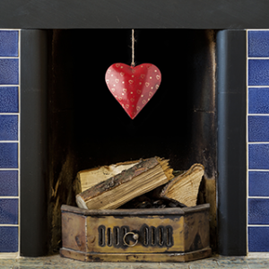 red metal hand painted heart dangling from blue tile fireplace