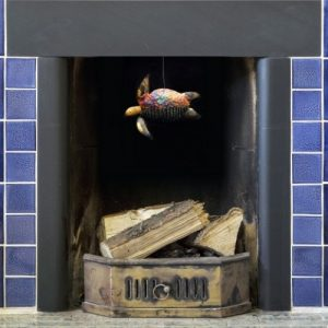 Iridescent tin and copper turtle hanging from blue tile fireplace - featuring colours of vivid blue purple and gold.