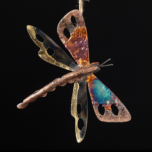 Tin and Copper iridescent dragonfly with vivid colours of blue and copper on a black background
