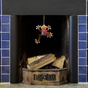 iridescent tin and copper frog dangling from a tiled blue fireplace