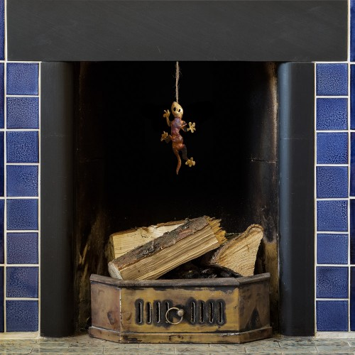 iridescent tin and copper gecko dangling from a tiled blue fireplace