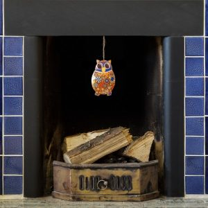 hand painted metal owl - blue dangling from a blue tiled fireplace