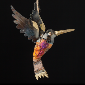 iridescent tin and copper hummingbird on a black background with vivid oranges and purples