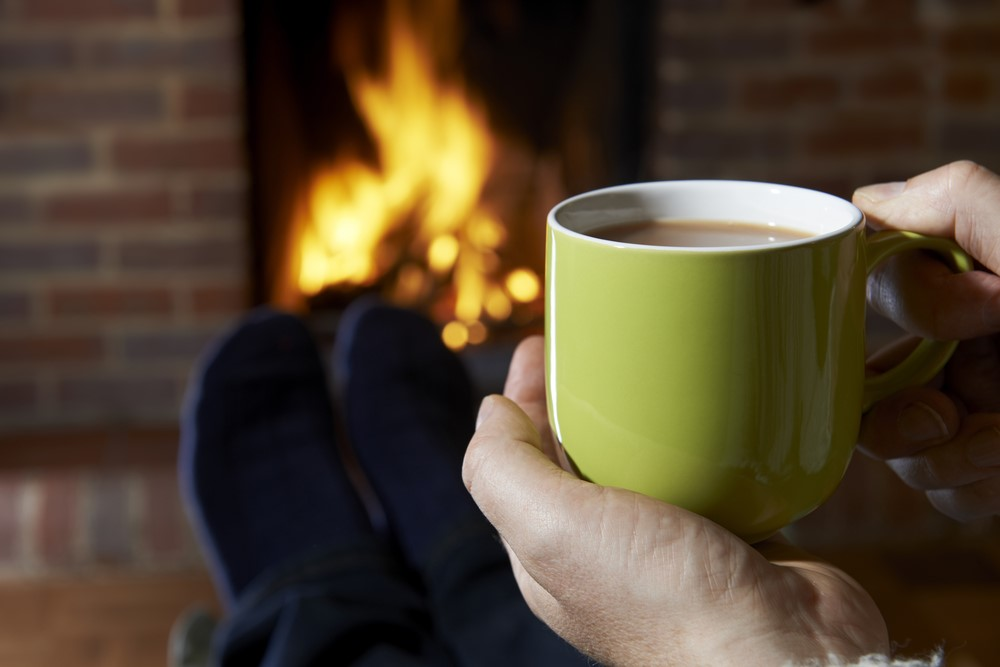 Drinking tea from a green cup infron of the fire - staying warm