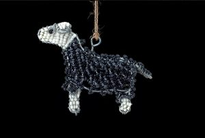 An close up of a beaded herdwick sheep dangle - colours of grey and white infront of a black background