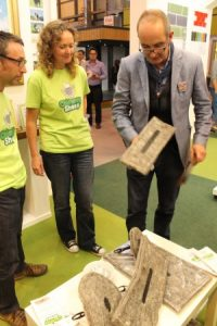 Image of Sally Phillips with Chimney Sheep being examined by Kevin McCloud