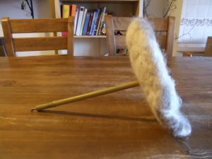A prototype chimney sheep made with felted wool and a bamboo handle
