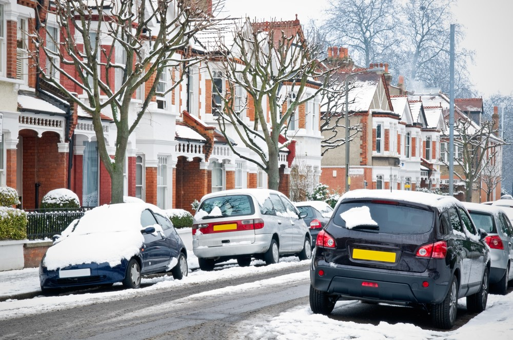 Snow fall on a typical british street showing houses and cars covered in snow.