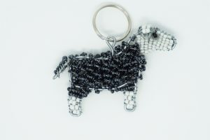 A beaded herdwick sheep dangle including colours of grey black and white placed in front of a white background