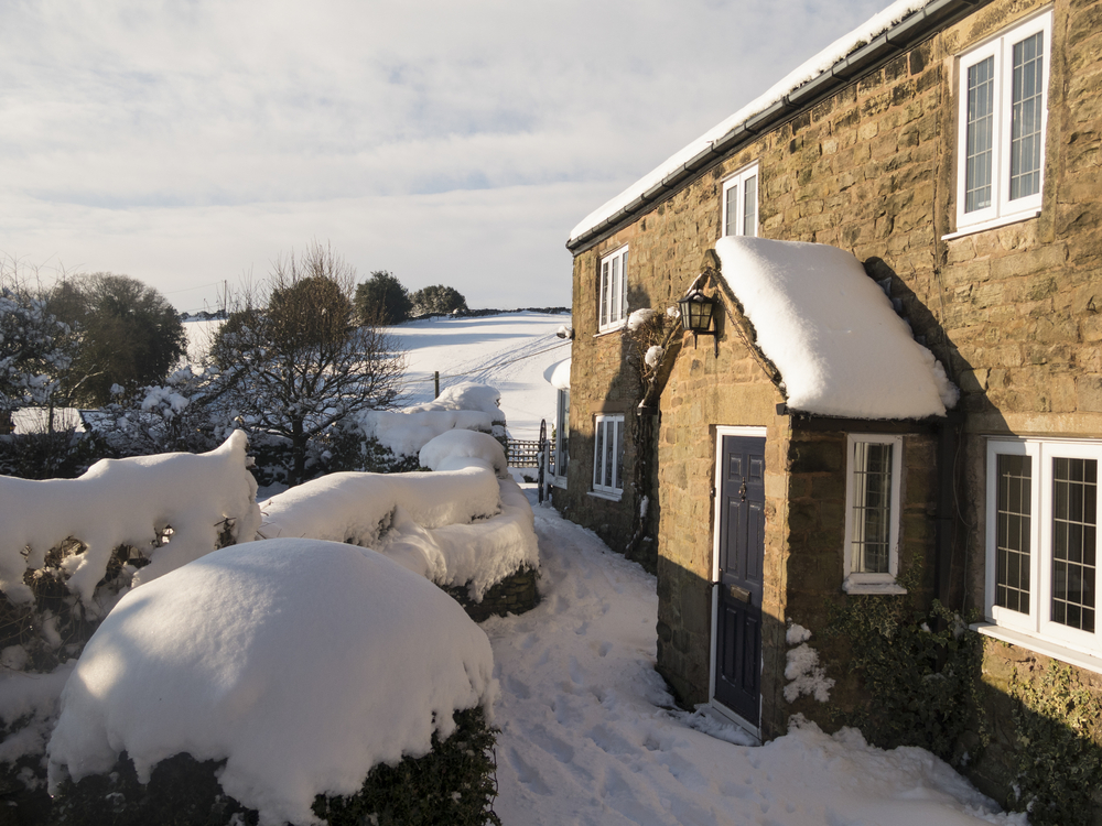A cold winter home - showing a large covering of snow with a picteresque background into some fields also covered in snow.