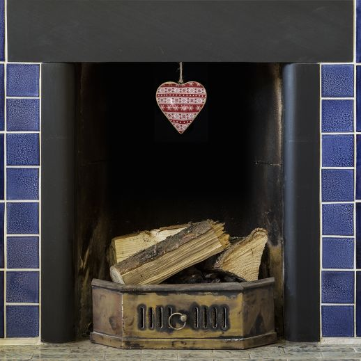 A nordic heart painted dangle in a blue tile fireplace. Includes a winter inspired design.