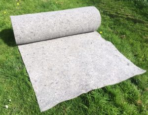 about a metre and a half of grey felt is unrolled onto sunlit grass. The rest of the roll, another 11 metres, is still rolled up, photo taken at an angle to the left