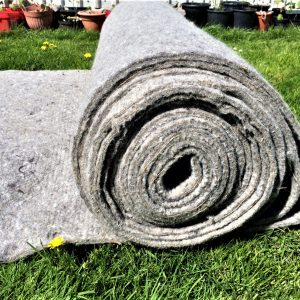 A large roll of wool felt with the image focusing on the side view of the roll. About a metre of felt is unrolled onto bright sunlit grass