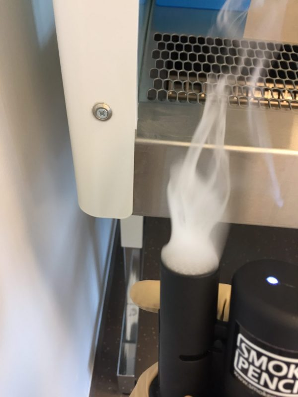 Smoke Pencil being held next to fume cupboard vent to check for air leaks -producing smoke