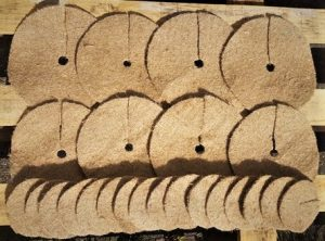 eight jute mulch mats eight inches in diameter and sixteen mulch mats four inches in diameter are laid out on a pallet in the sunshine