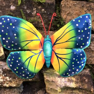 A giant multicoloured metal butterfly - made from upcycled oil drums, sitting on a garden wall. A multi coloured butterfly garden ornament.