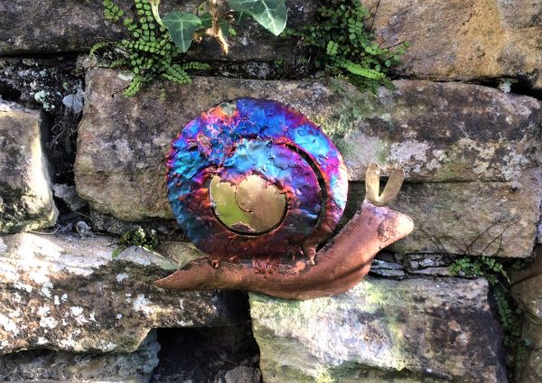 Copper ornamental snail with copper coloured body and iridescent blues, purples, on the curly shell, placed on the garden wall.