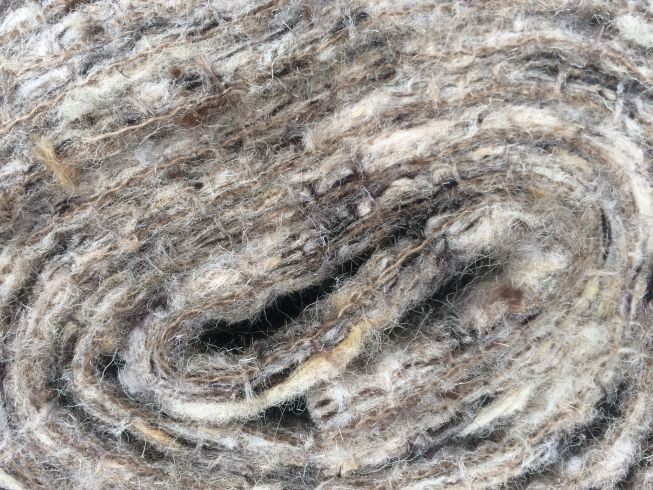 close-up of mixed wool on a roll for pure wool underlay felted onto jute for an all natural product