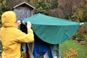A woman wearing a yellow raincoat hangs laundry on a rotary dryer then covers it with a green Laundry Mac which protects the laundry from the rain