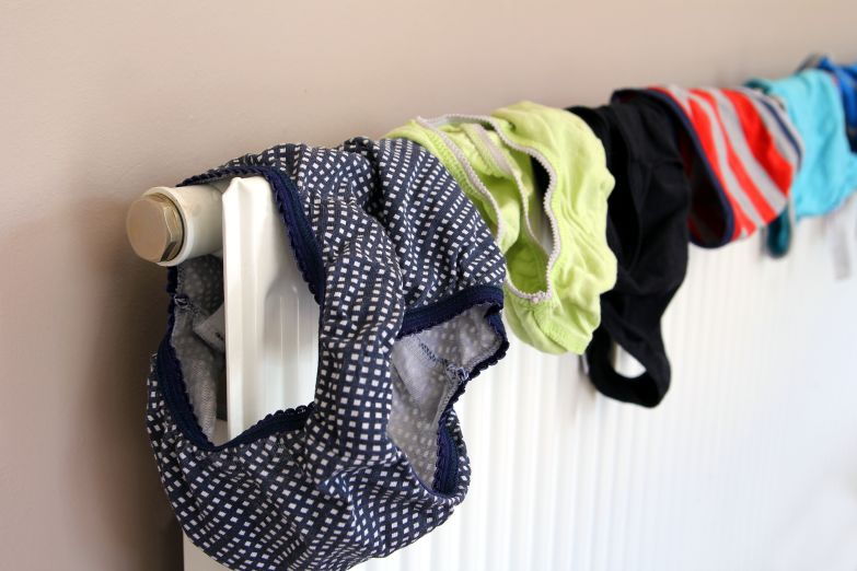line of pants hung on a radiator causing damp in the home