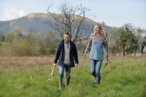 Sally Phillips and Darren Ward walk through field bought by Chimney Sheep to offset CO2