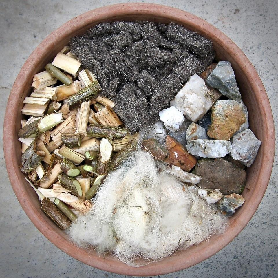 A Plant pot containing Chimney Sheeps felt shillies along with tree bark sheeps wool and rocks