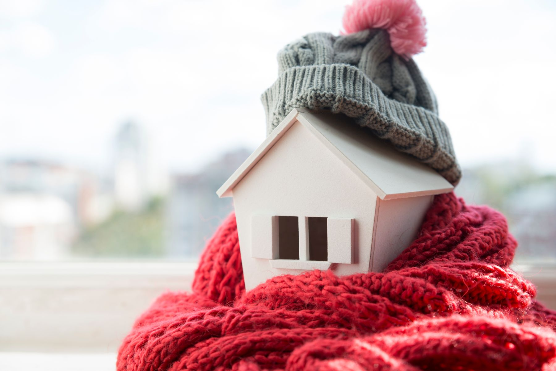 sheep wool insulation illustrated by a model of a house wrapped in a cosy red scarf and grey bobble hat