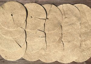 "10"" / 25cm jute mulch mat pack of 20 laid out flat on a grid"
