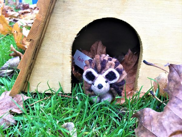 felted hedgehog peaking out of hedgehog house