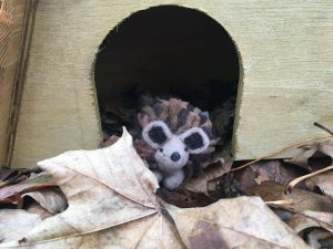 felted hedgehog peaking out of a hedgehog house