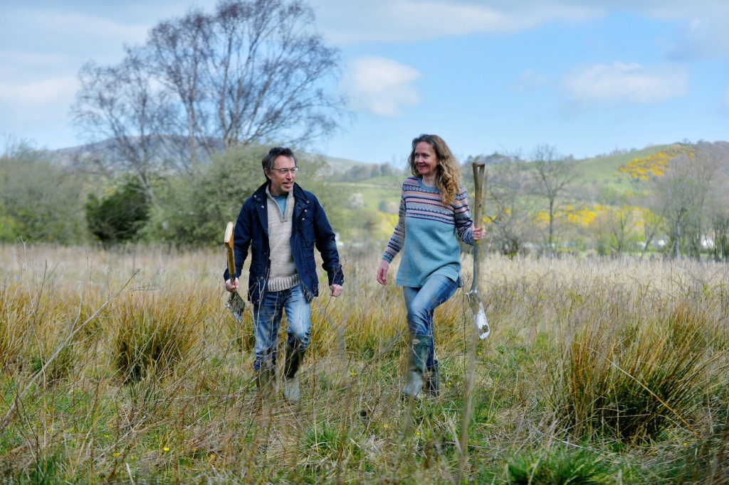 Chimney Sheep owner Sally and colleague walk across a lake district field overgrown with rushes carrying spades, discussing their tree planting plans